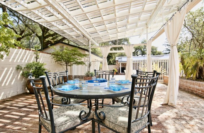 Outdoor patio with brick floor, wooden shade awning, privacy curtains, patio furniture and table setting