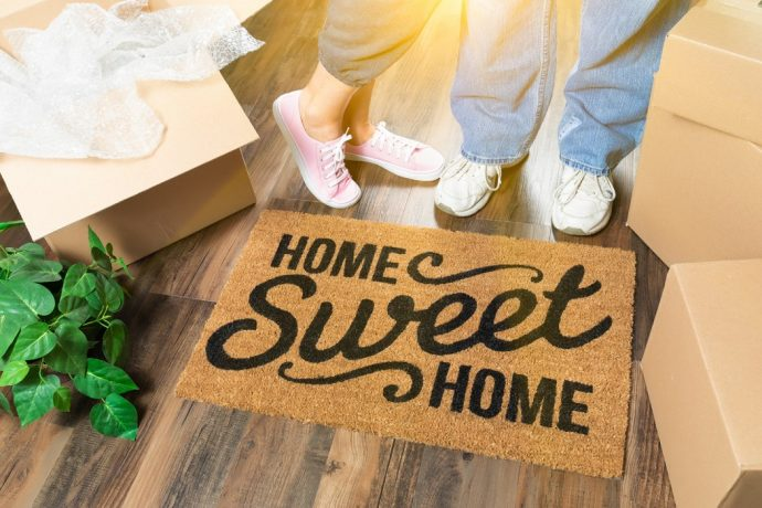 Man and Woman Standing Near Home Sweet Home Welcome Mat, Moving Boxes and Plant