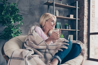 Women snug and warm sat on chair with hot drink